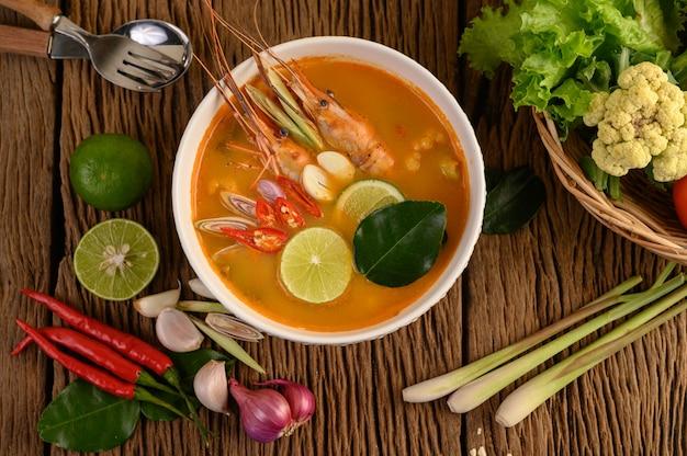 Tom yum kung тайский горячий острый суп из креветок с лимонной травой, лимоном, галангалом и чили на деревянном столе, таиландская еда Бесплатные Фотографии