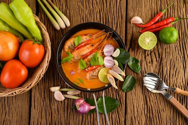 トムヤムクンタイホットスパイシーなスープエビとレモングラス、レモン、ガランガル、唐辛子、木製のテーブル、タイ料理 無料写真
