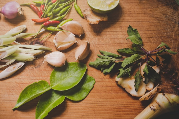 Tom yum spices that are placed on a brown wood cutting board and have a dark brown wood . Free Photo