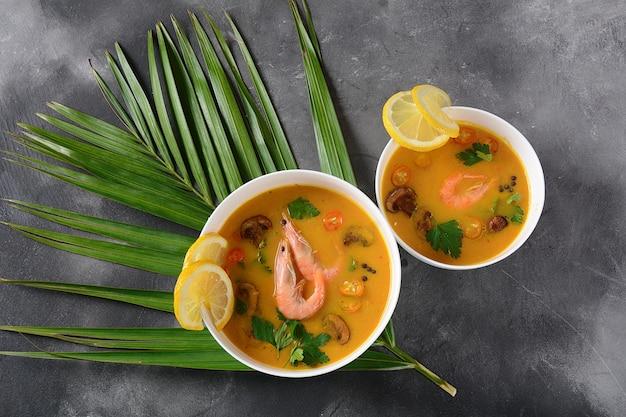 Tom yum - традиционный острый тайский суп с кокосовым молоком, перцем чили, лимоном, грибами. азиатский суп Premium Фотографии