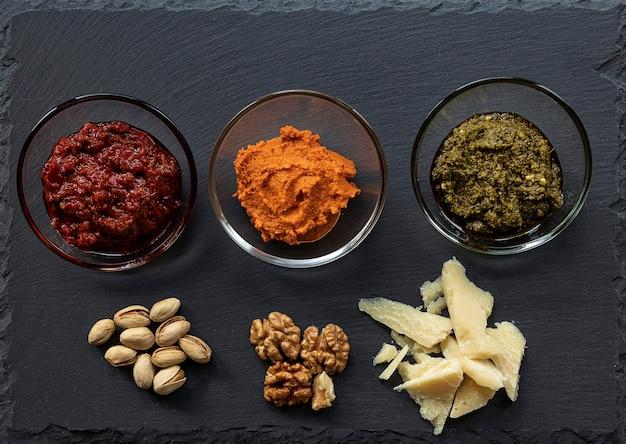 ダークスレートチーズボードにトマトとマスカルポーネソース、パルメザンチーズ、ハリッサペースト、ナッツ、ペストソース Premium写真