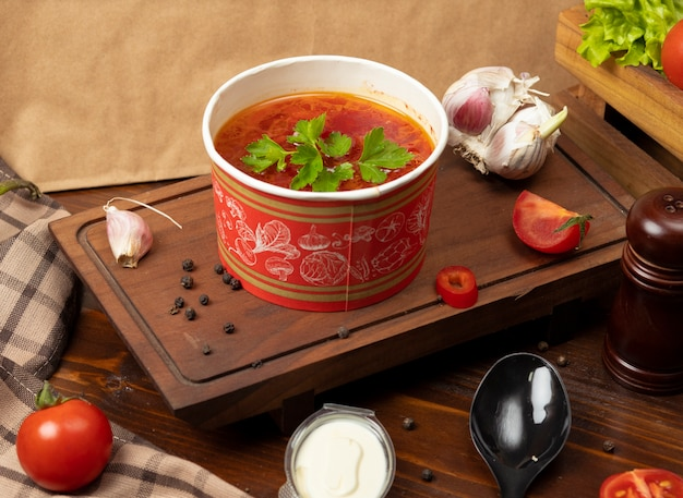 Tomato, borsh vegetable soup in disposable cup bowl served with green vegetables. Free Photo