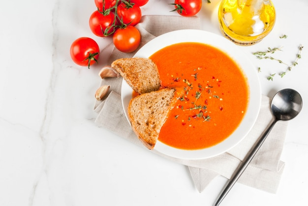 Tomato cream soup with olive oil and herbs, with toasted bread, on white marble ,  top view Premium Photo