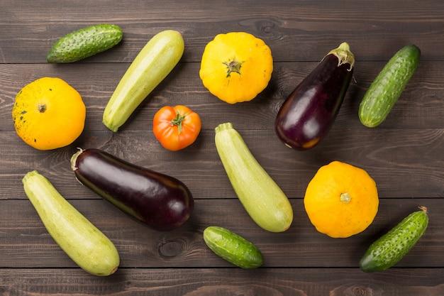 Tomato, cucumbers, bush pumpkins, eggplants nd marrows on dark wooden table. Premium Photo