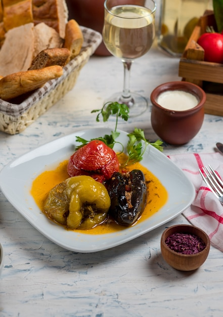Tomato, green bell pepper and eggplants stuffed with meat and rice, vegetables in oil sauce, dolma. Free Photo