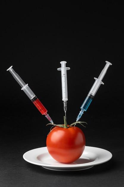 3本の注射器でトマトを注入 Premium写真