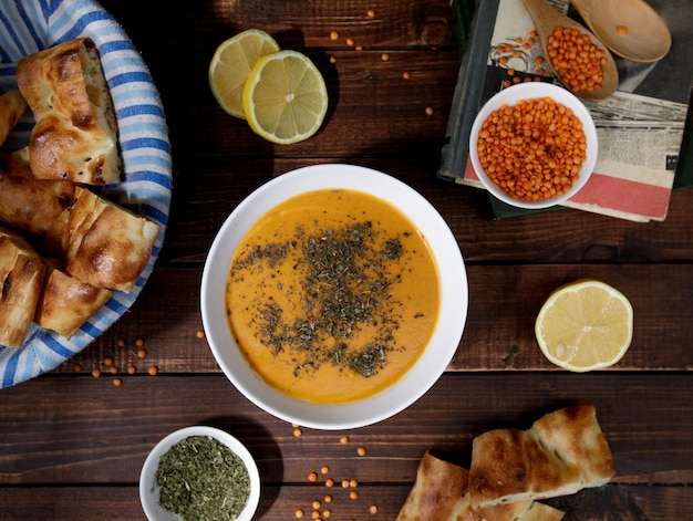 Tomato lentil soup with herbs in a white bowl served with bread, top view Free Photo