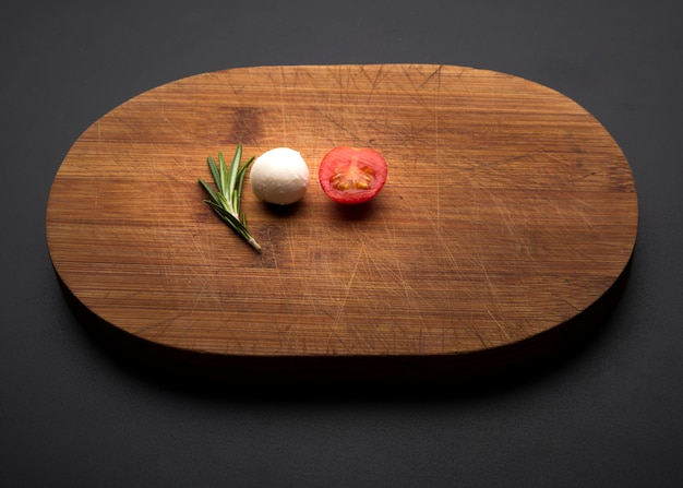 Tomato; rosemary and cheese on wooden cutting board over black background Free Photo