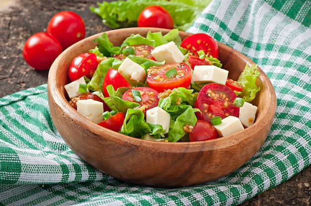 Tomato salad with lettuce, cheese and mustard and garlic dressing Free Photo