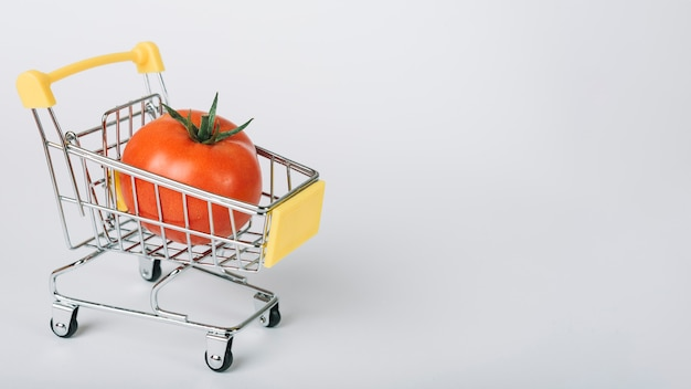 Tomato in shopping cart on white surface Free Photo