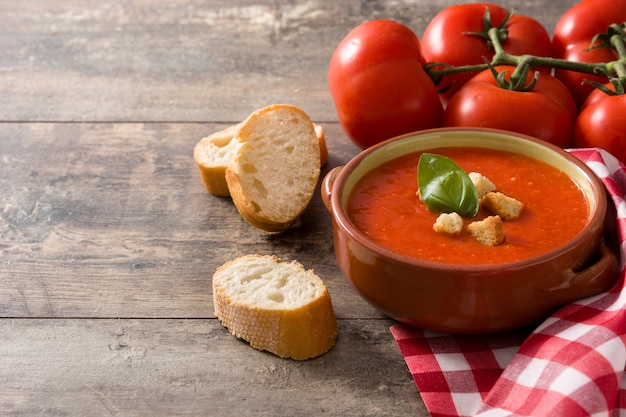 Tomato soup in brown bowl on wooden table copy space Premium Photo