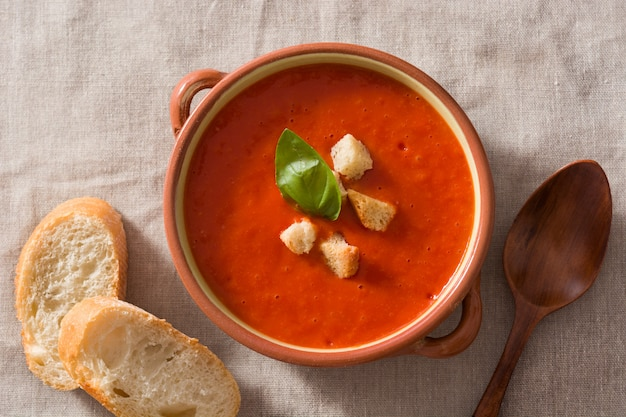 Tomato soup in brown bowl on wooden table top view Premium Photo