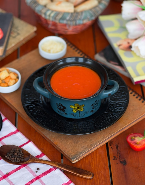 Tomato soup in a pot with chopped parmesan cheese and bread crackers Free Photo