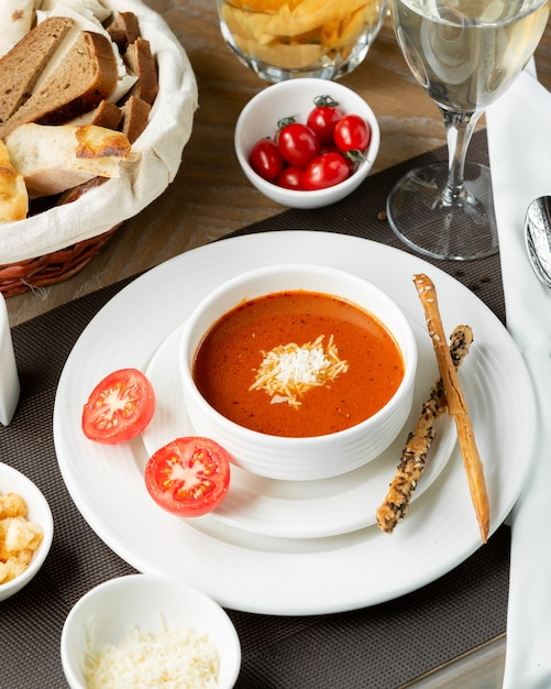 Tomato soup with chopped cheese and galetta sticks. Free Photo
