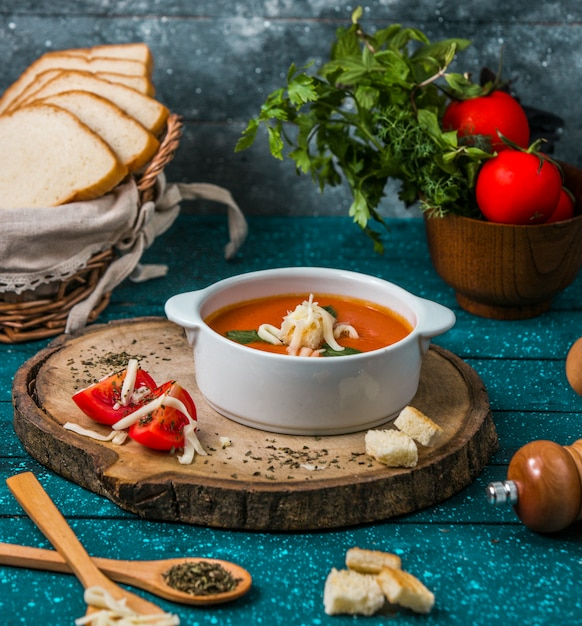 Tomato soup with parmesan on a piece of woode with tomatoes and crackers around. Free Photo