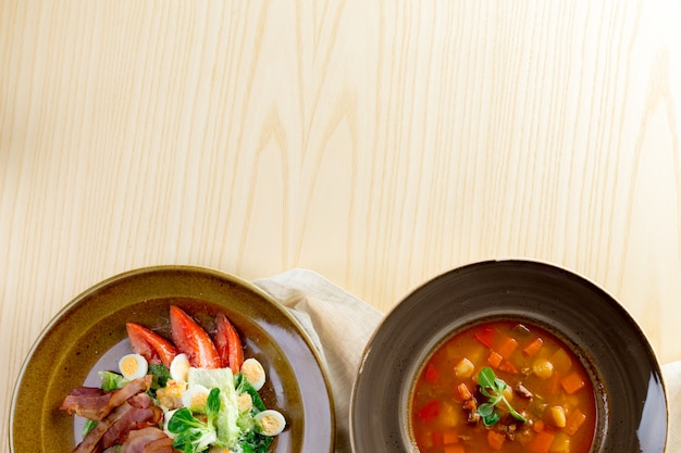 Tomato soup on wooden table, top view Premium Photo