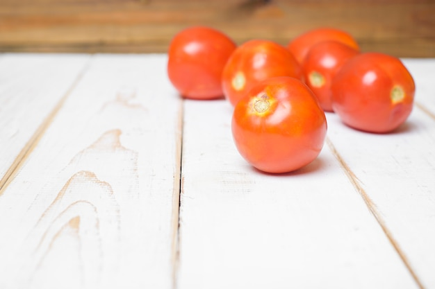 Tomato on white wooden background. Premium Photo