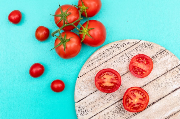 Tomato on wooden board branch of cherry tomato on blue surface top view Free Photo
