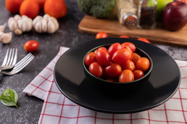The tomatoes are in the black cup Free Photo