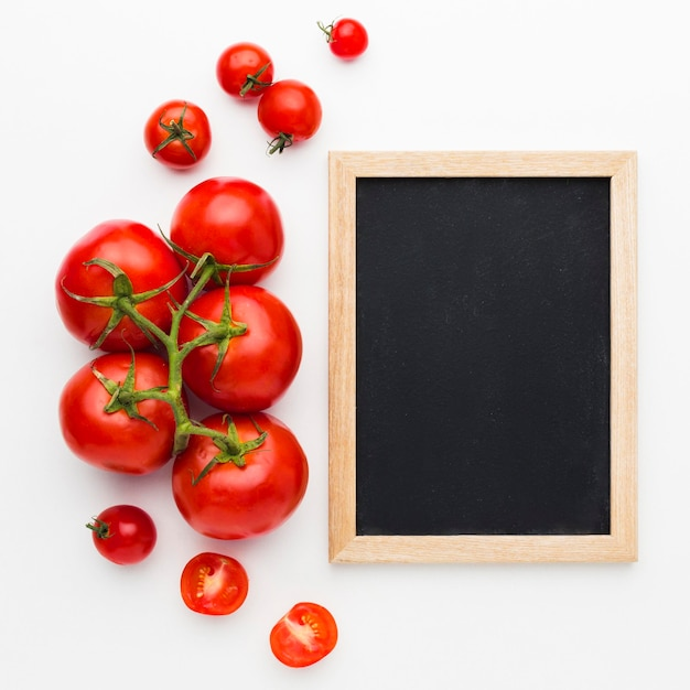 Tomatoes arrangement with empty blackboard Free Photo