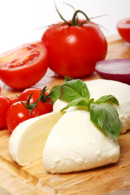 Tomatoes, basil and mozzarella on wooden board Free Photo