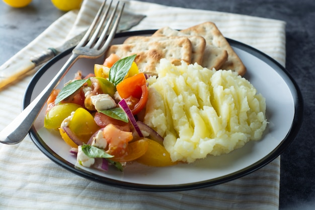 Tomatoes fresh salad and mushed potatoes in a plate. healthy, summer food. Premium Photo
