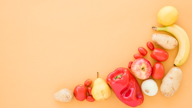 Tomatoes; potatoes; pears; banana; apple and lime on beige background Free Photo