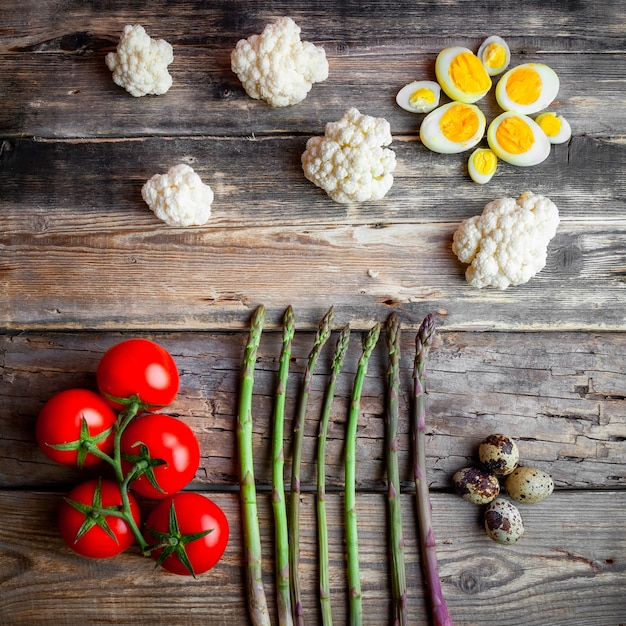 Tomatoes with asparagus, eggs, cauliflower top view on a dark wooden background Free Photo
