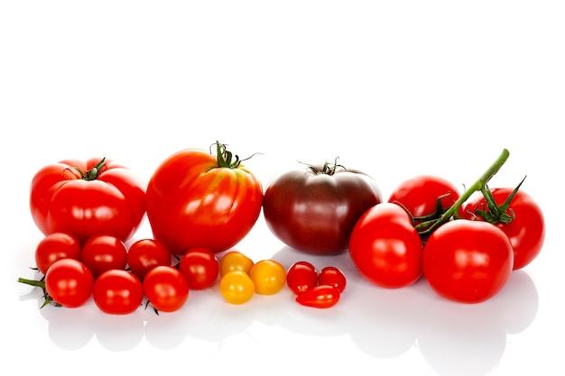 白い背景で隔離の緑の葉を持つトマト Premium写真