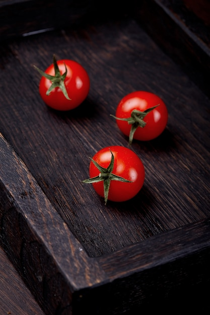 Tomatoes in a wooden box on the wooden table. tomatoes on a wooden background. Premium Photo