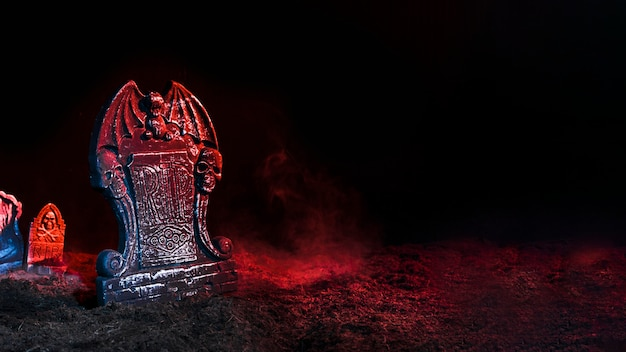 Tombstones illuminated by red light on soil Free Photo