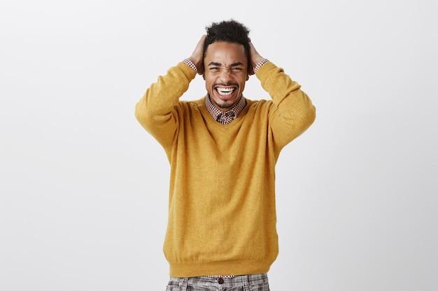 Слишком сильная боль для одной головы. портрет недовольного неудобного привлекательного афроамериканца в желтом свитере, держащего руки за волосы, гримасничающего и щурящегося, ощущающего дискомфорт и головную боль Бесплатные Фотографии