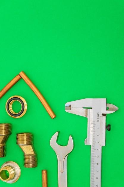 緑の背景に分離された配管用ツールとスペアパーツ Premium写真