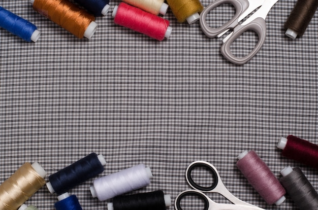 Tools and accessories for sewing. sewing thread, scissors on gray Premium Photo