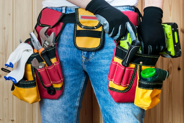 Tools in the belt for tools. the builder is holding an electric screwdriver Premium Photo