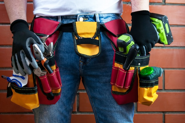 Tools in the belt for tools. the builder is holding an electric screwdriver. Premium Photo
