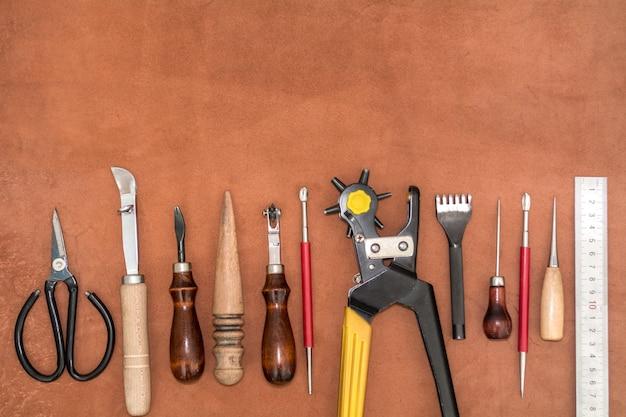 Инструменты для поделок и кусочки коричневой кожи Premium Фотографии