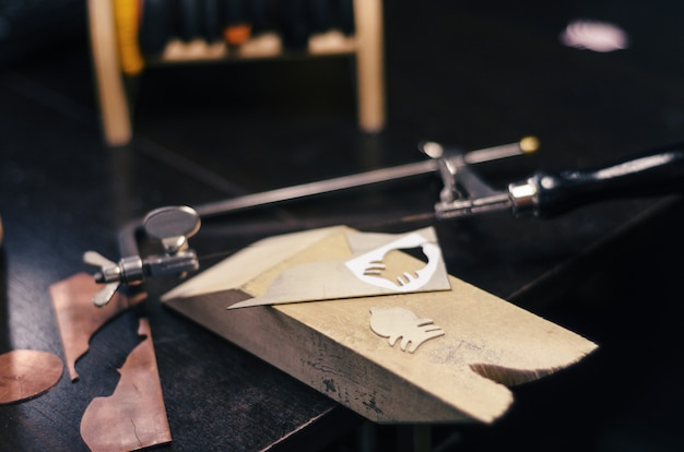 Tools for home-made jewelry on the desktop table. jig saw, metal, shape, detail, finagel Premium Photo