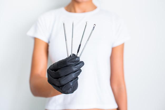 Tools for removing acne. tools of the cosmetologist for problem skin in woman's hand in black glove. Premium Photo
