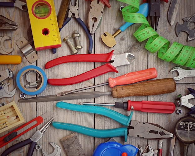 Tools scattered on the wooden floor, top view. Premium Photo
