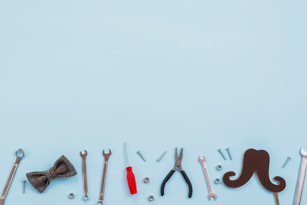 Tools with bow tie and paper mustache Free Photo