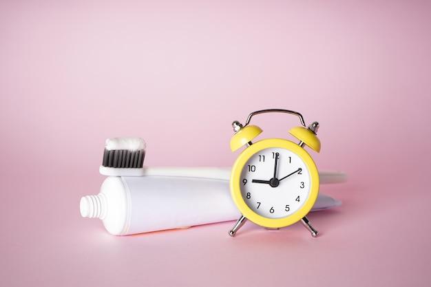 ピンクの目覚まし時計付き歯ブラシと歯磨き粉 Premium写真