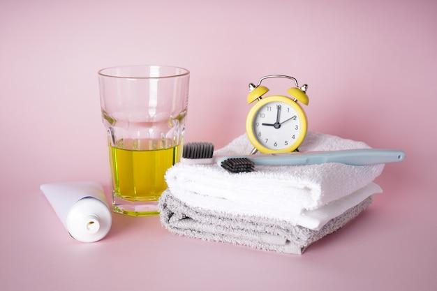 ピンクの目覚まし時計付き歯ブラシとタオル Premium写真