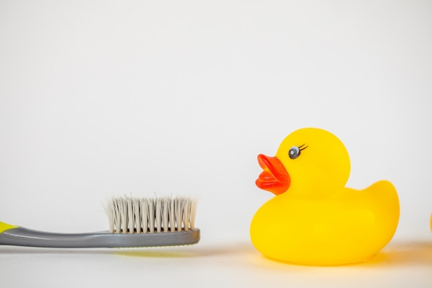 Toothbrush with clear cup and yellow rubber duck on white. Premium Photo