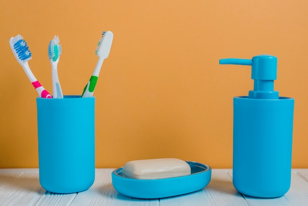 Toothbrushes soap and soap dispenser bottle on white desk against wall Free Photo