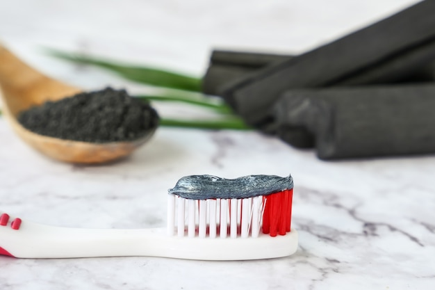 Toothpaste by activated charcoal powder on marble table Premium Photo