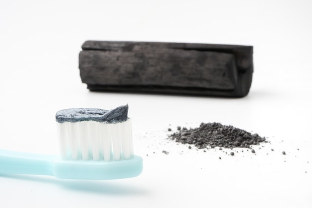 Toothpaste by activated charcoal powder on white background Premium Photo