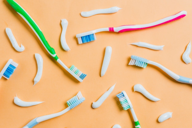 Toothpaste with different type of toothbrushes on colored background Free Photo