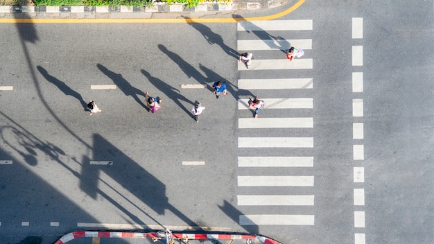 Top aerial view of group people walk at street city with pedestrian crosswalk in transport traffic road. Premium Photo