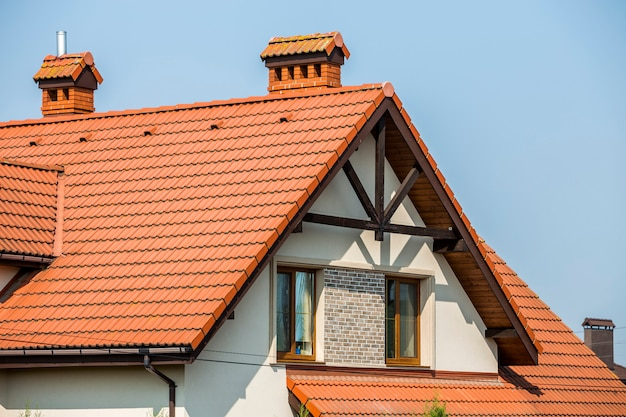Top of big modern expensive residential house cottage with steep shingled brown roof, high brick chimneys, stucco walls, gutter system and plastic attic windows on blue sky Premium Photo